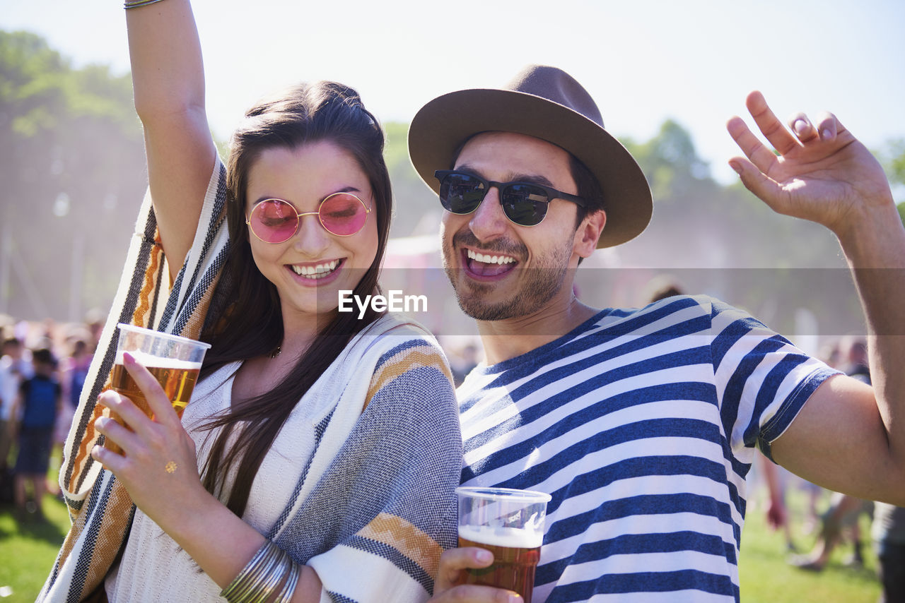 emotion, young adult, happiness, young men, togetherness, two people, drink, fashion, leisure activity, real people, casual clothing, smiling, adult, glasses, young women, sunglasses, friendship, portrait, men, refreshment, drinking, couple - relationship, positive emotion, outdoors, glass