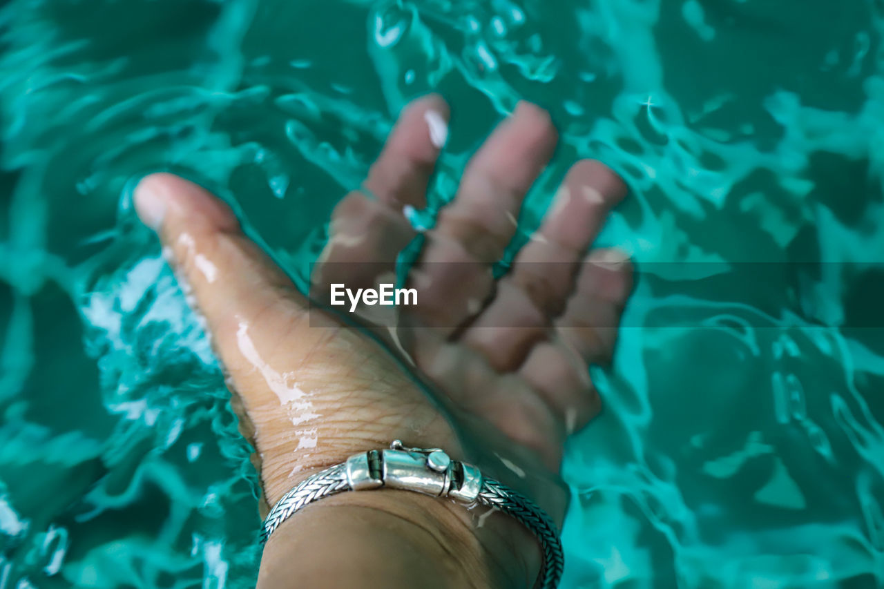 High angle view of woman hand in swimming pool