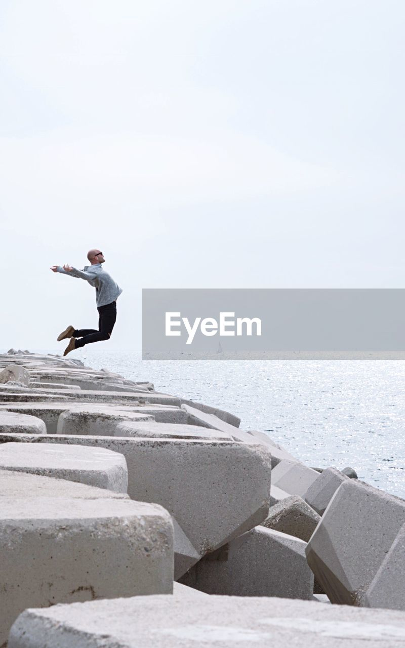 Side View Of Man Jumping On Beach