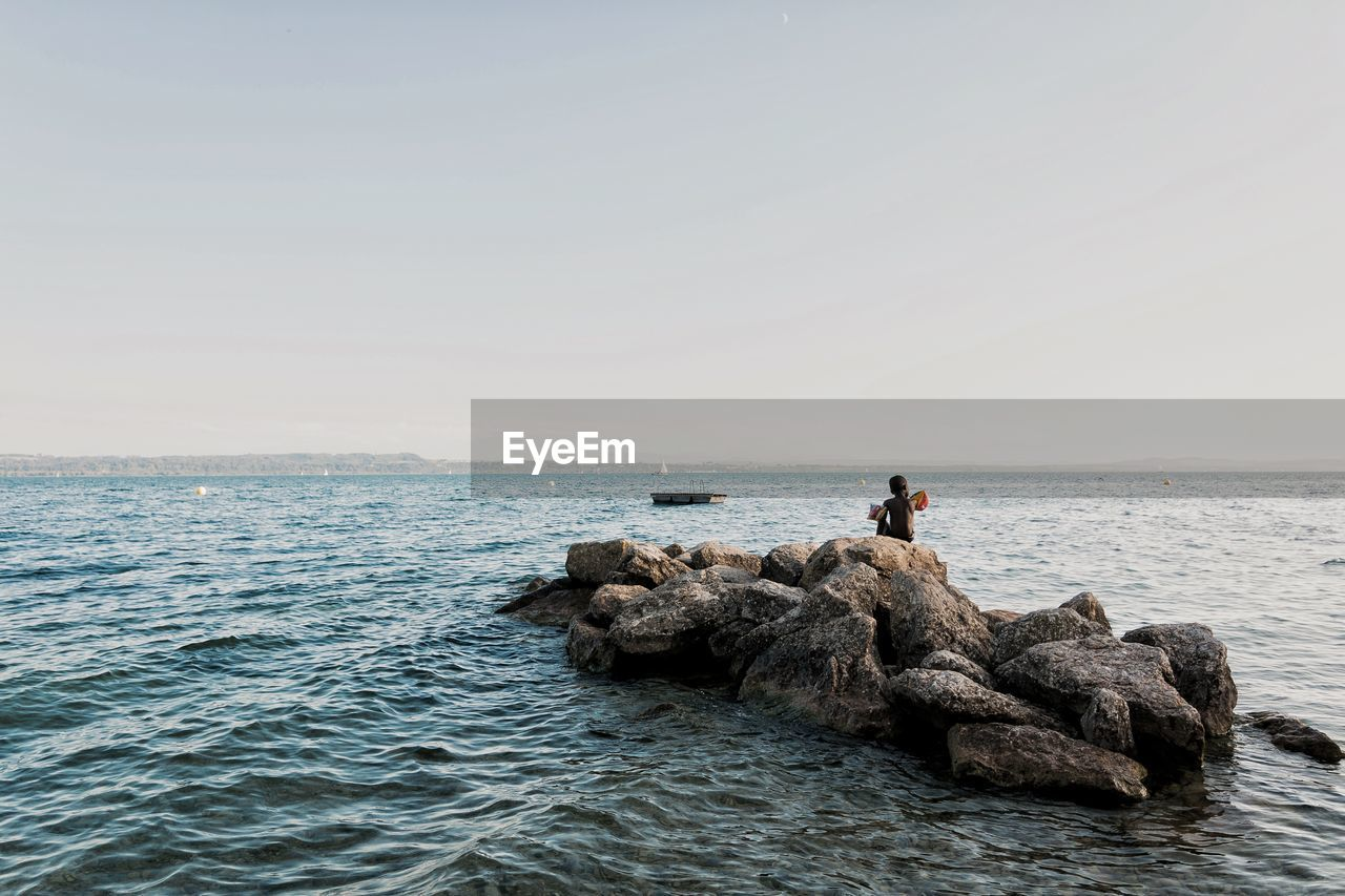 sea, water, sky, horizon, horizon over water, scenics - nature, beauty in nature, real people, clear sky, rock - object, rock, solid, tranquility, waterfront, tranquil scene, copy space, nature, leisure activity, lifestyles, outdoors