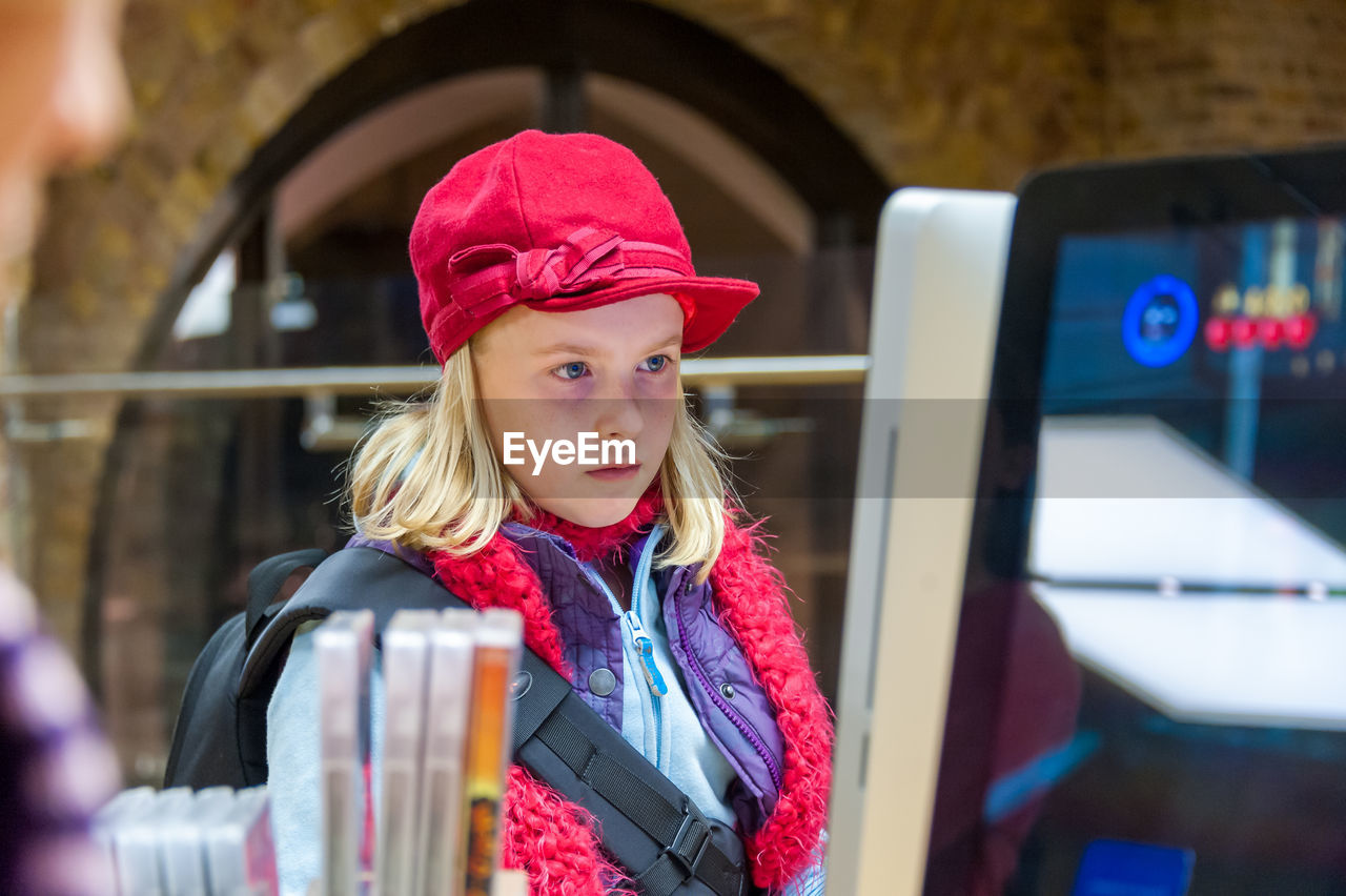 A young girl wearing a red hat sat at a computer monitor.