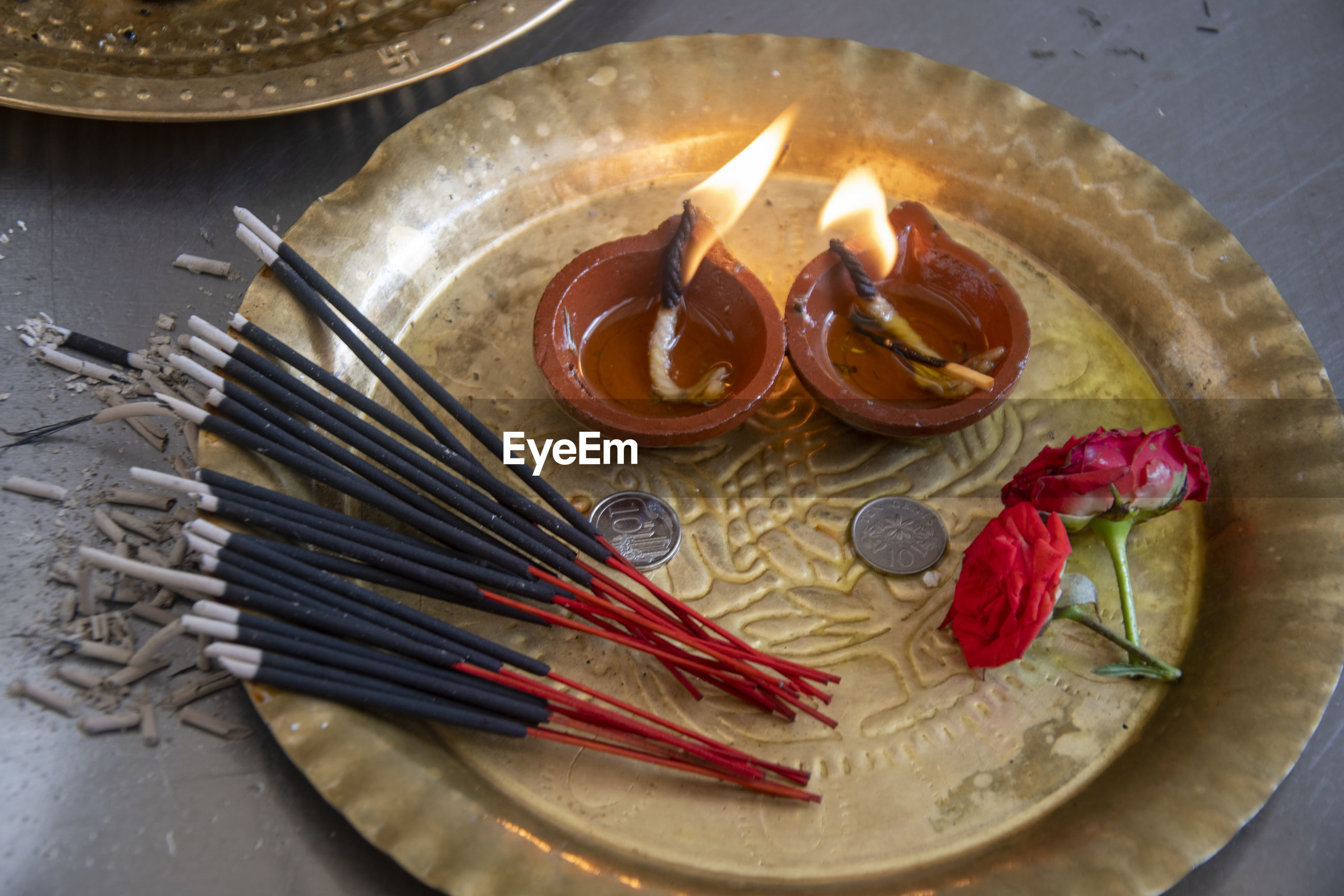 High angle view of lit diya and incense sticks on plate
