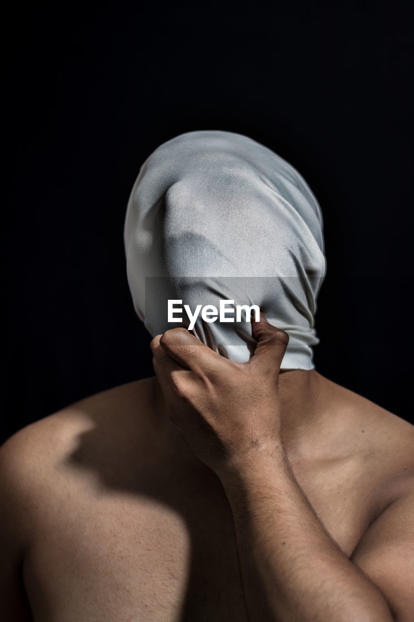 Shirtless man covering face with t-shirt against black background
