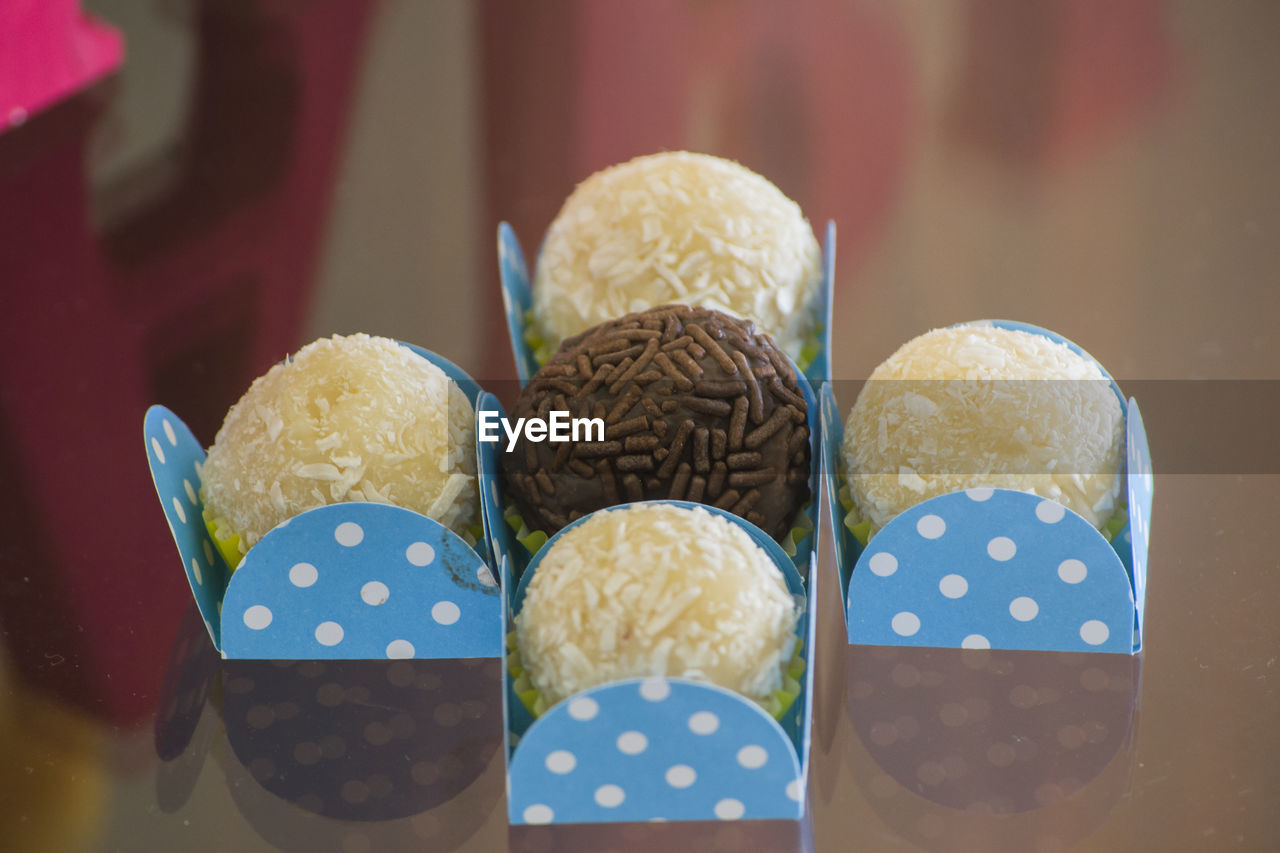 Close-Up Of Chocolate Candies In Containers On Table