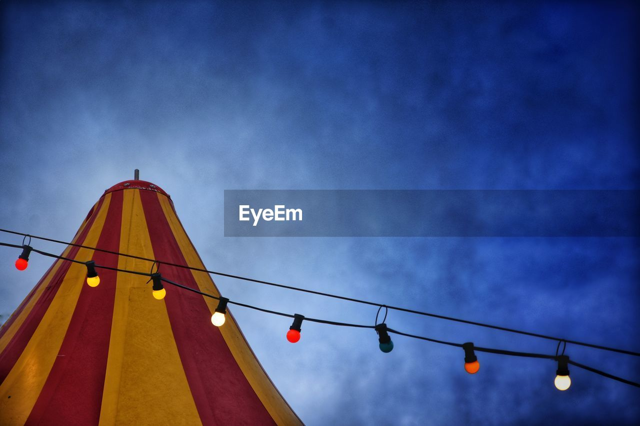 low angle view, sky, lighting equipment, cloud - sky, nature, no people, hanging, blue, dusk, red, outdoors, architecture, arts culture and entertainment, cable, built structure, circus, light, illuminated, electricity, rope