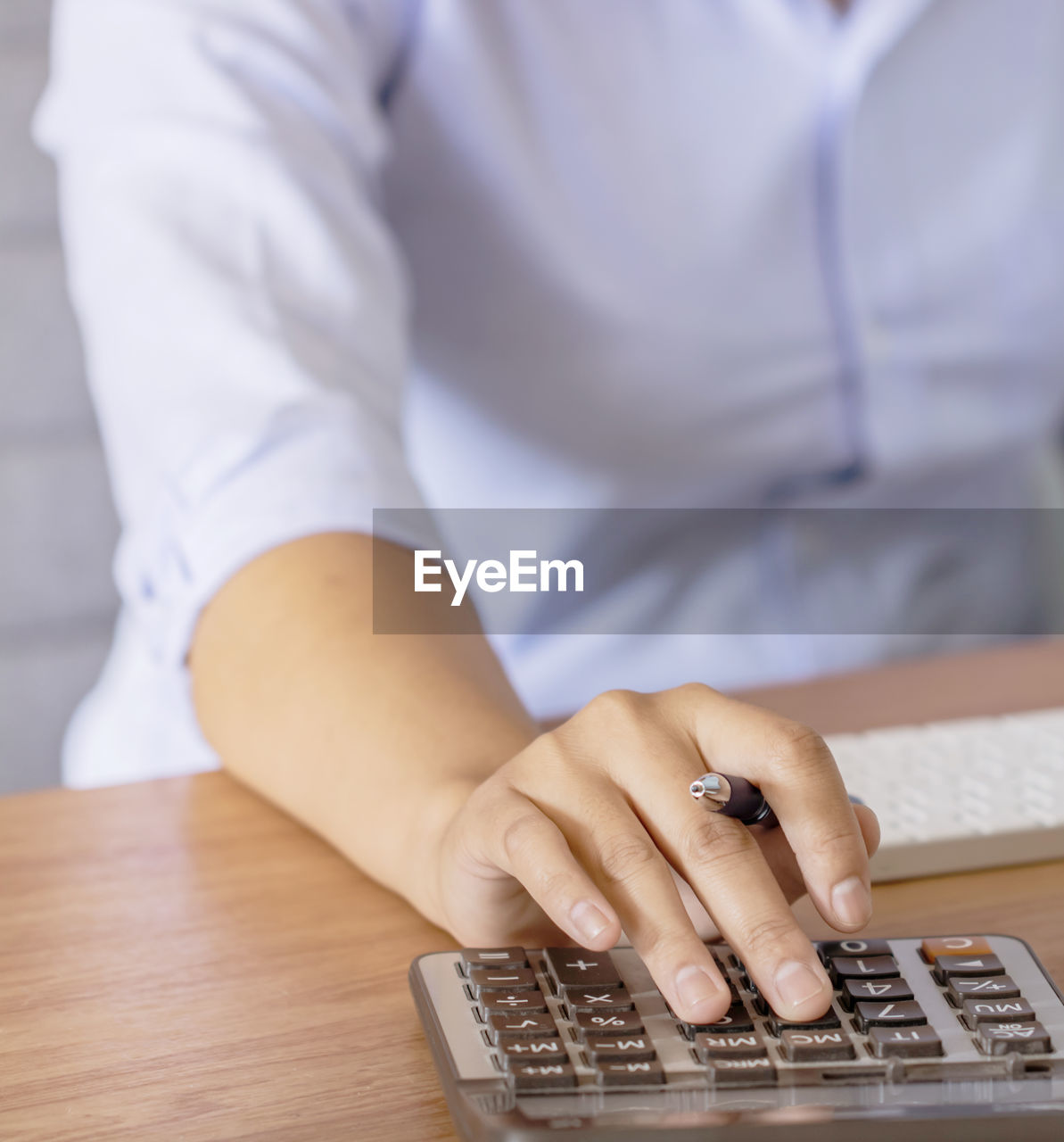 Midsection of businesswoman using calculator on table