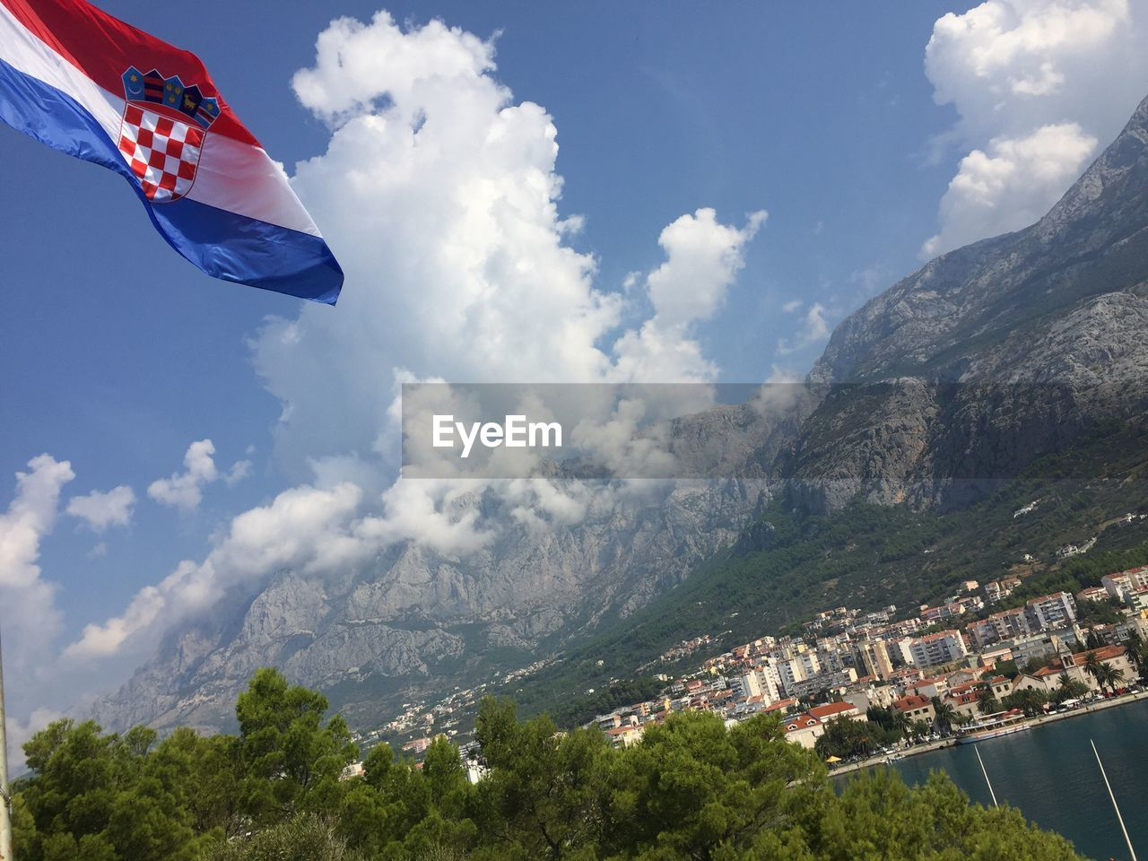 Low angle view of croatian flag and mountain against sky