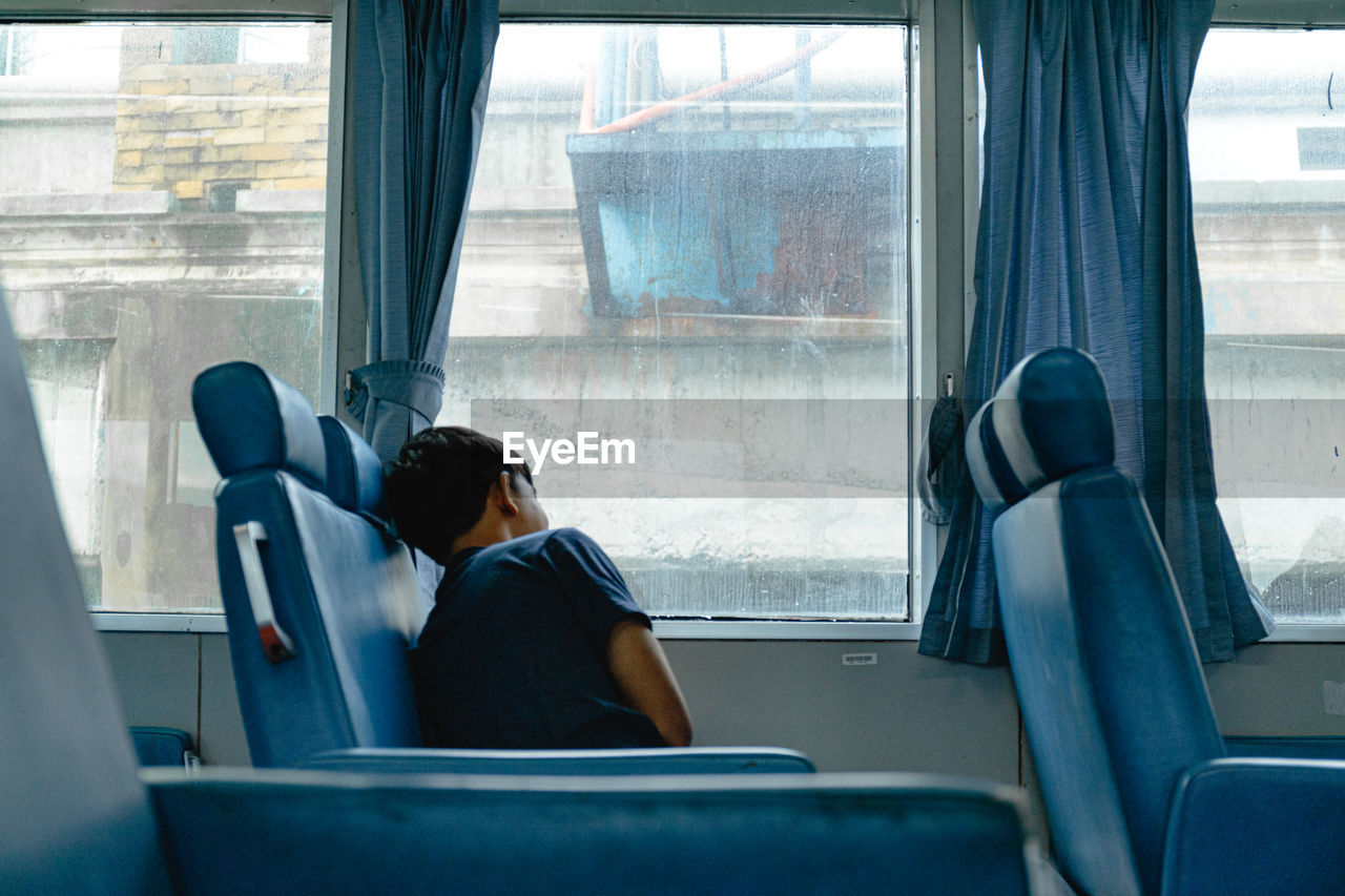 Man looking through window while sitting in train