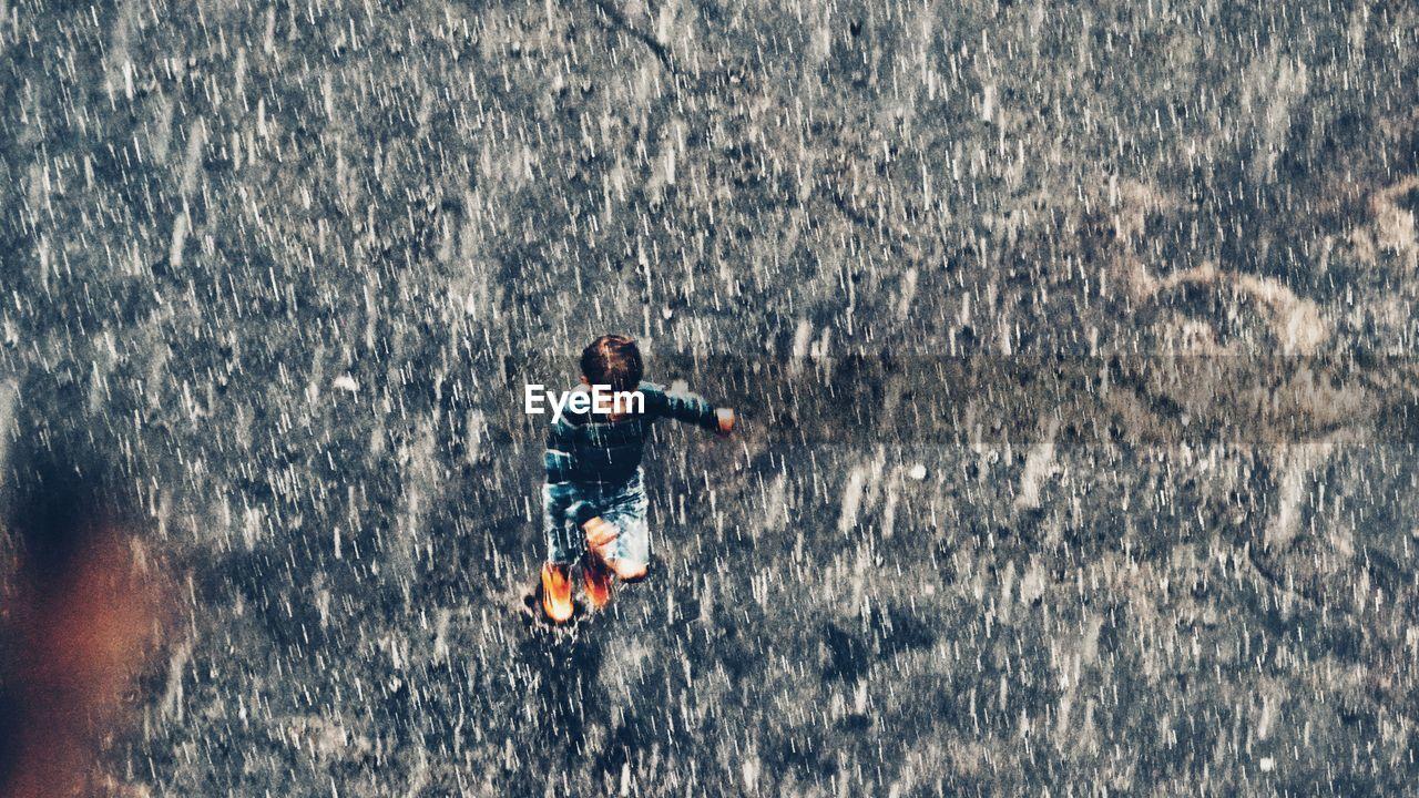 High Angle View Of Boy Running On Street During Rainy Season