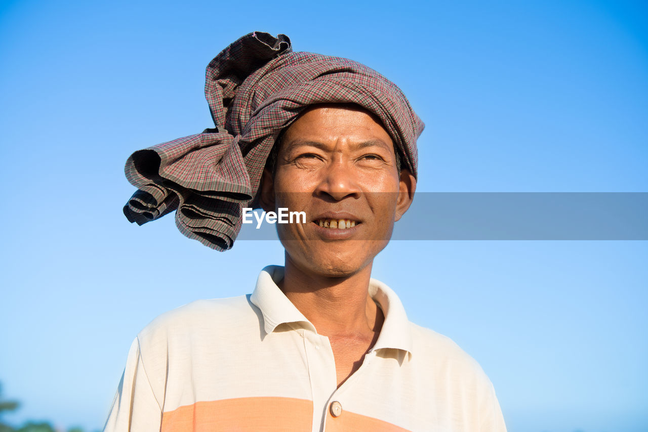 Low angle of man looking away against clear blue sky