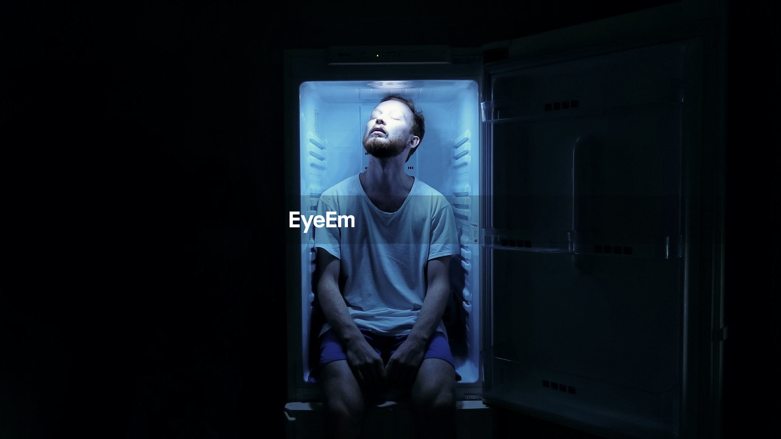 Portrait of man sitting in fridge