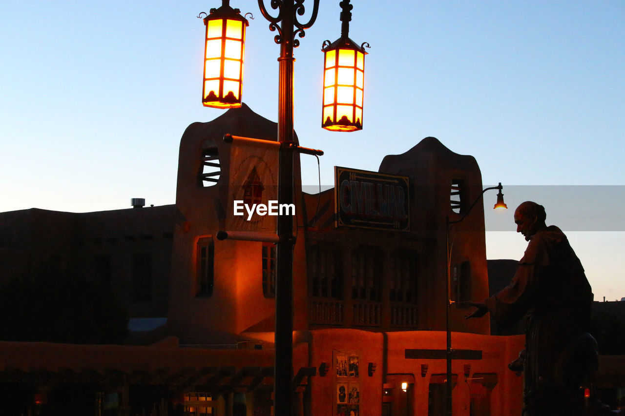 Low Angle View Of Illuminated Street Light Against Building At Dusk