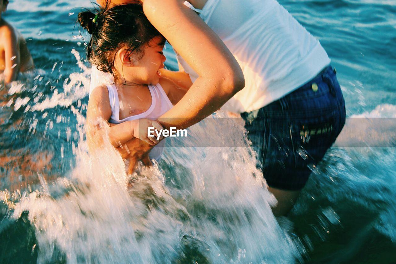 water, child, motion, childhood, real people, leisure activity, splashing, sea, women, two people, females, girls, nature, fun, lifestyles, enjoyment, blurred motion, outdoors