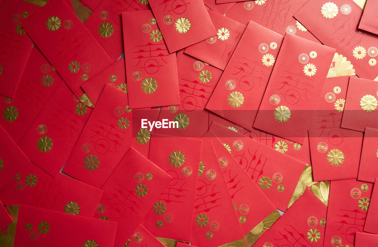 red, full frame, backgrounds, no people, pattern, decoration, indoors, design, close-up, text, floral pattern, art and craft, repetition, textile, celebration, still life, high angle view, chinese new year, festival