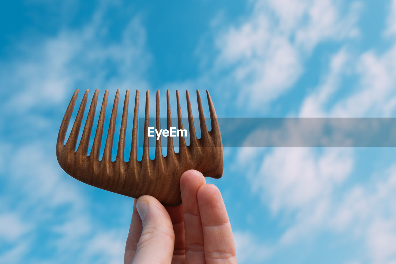 Close-up of hand holding comb against sky