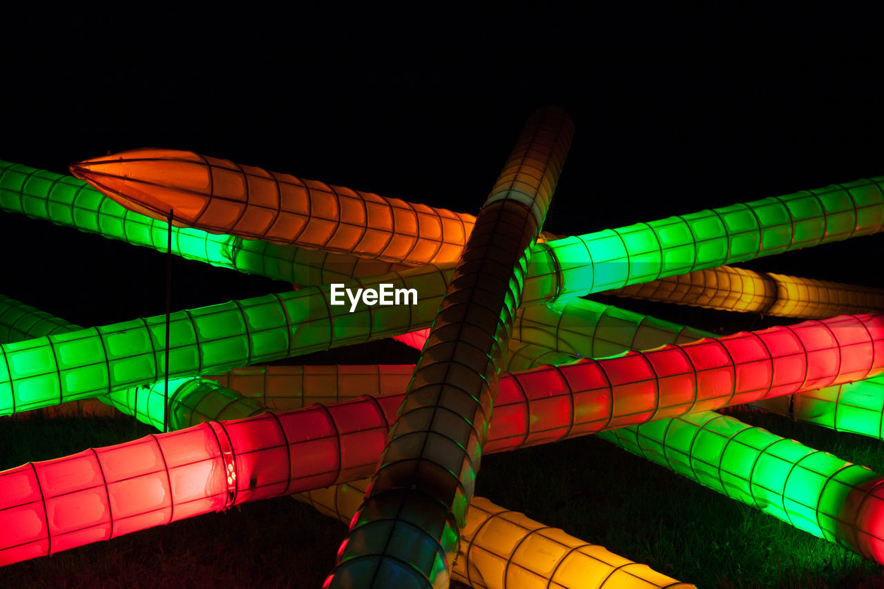 multi colored, pattern, no people, illuminated, low angle view, night, close-up, green color, lighting equipment, indoors, striped, art and craft, geometric shape, yellow, glowing, creativity, variation, sky, choice, vibrant color