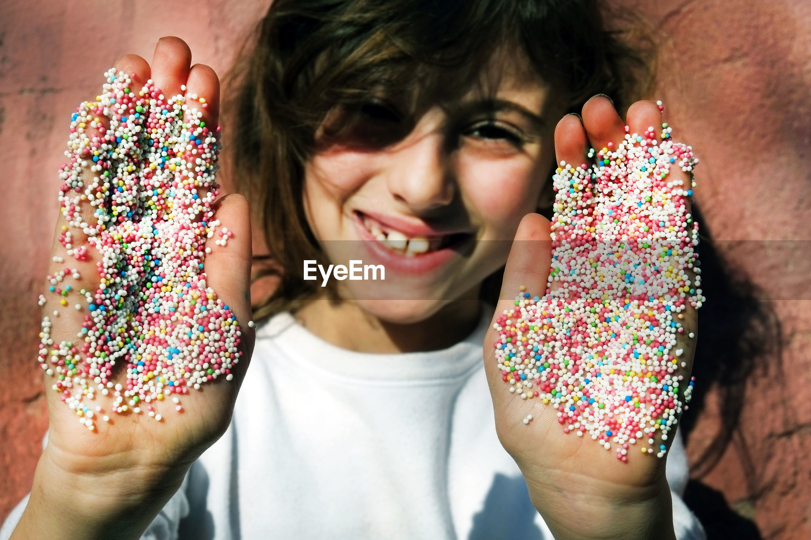 Portrait of smiling woman with multi colored candies on hand