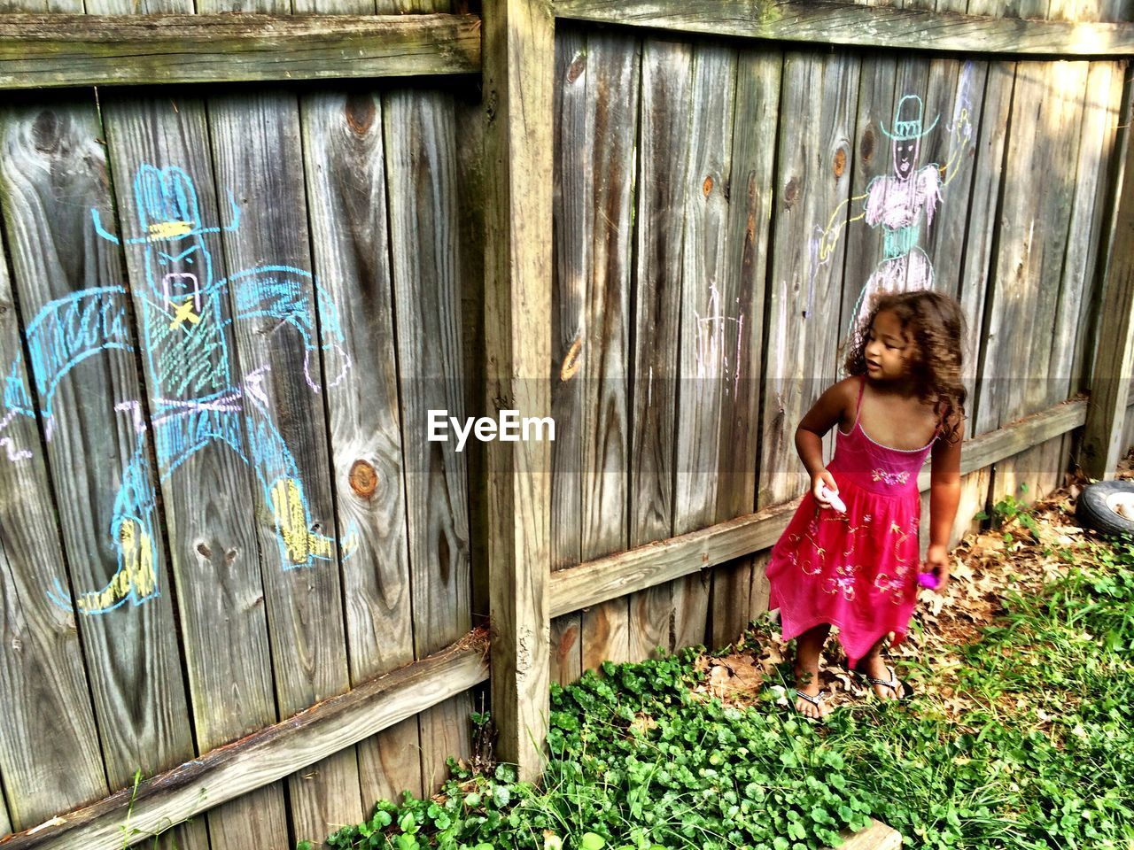 Cute girl making chalk drawing on wooden fence