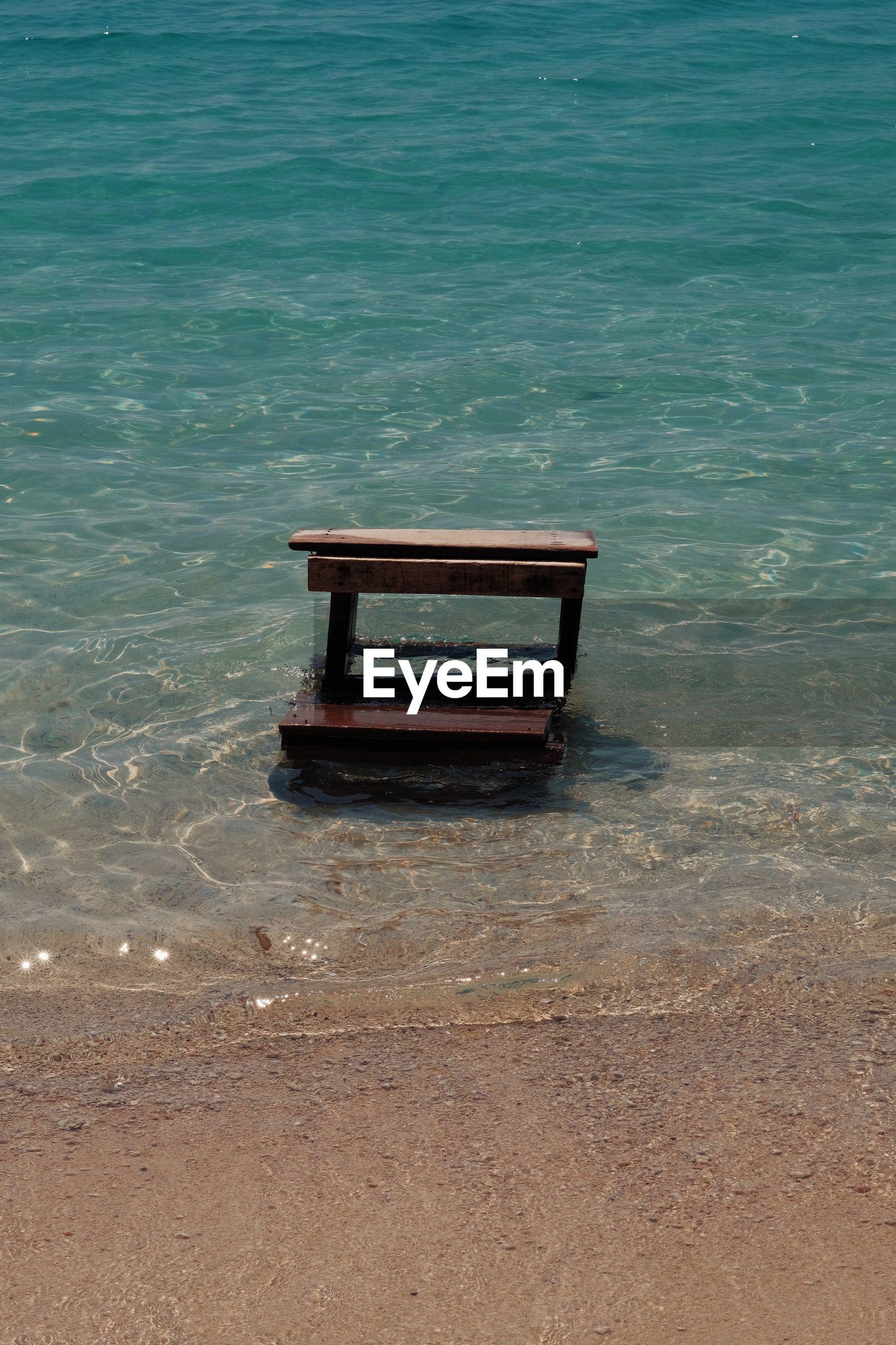 EMPTY BENCH ON BEACH