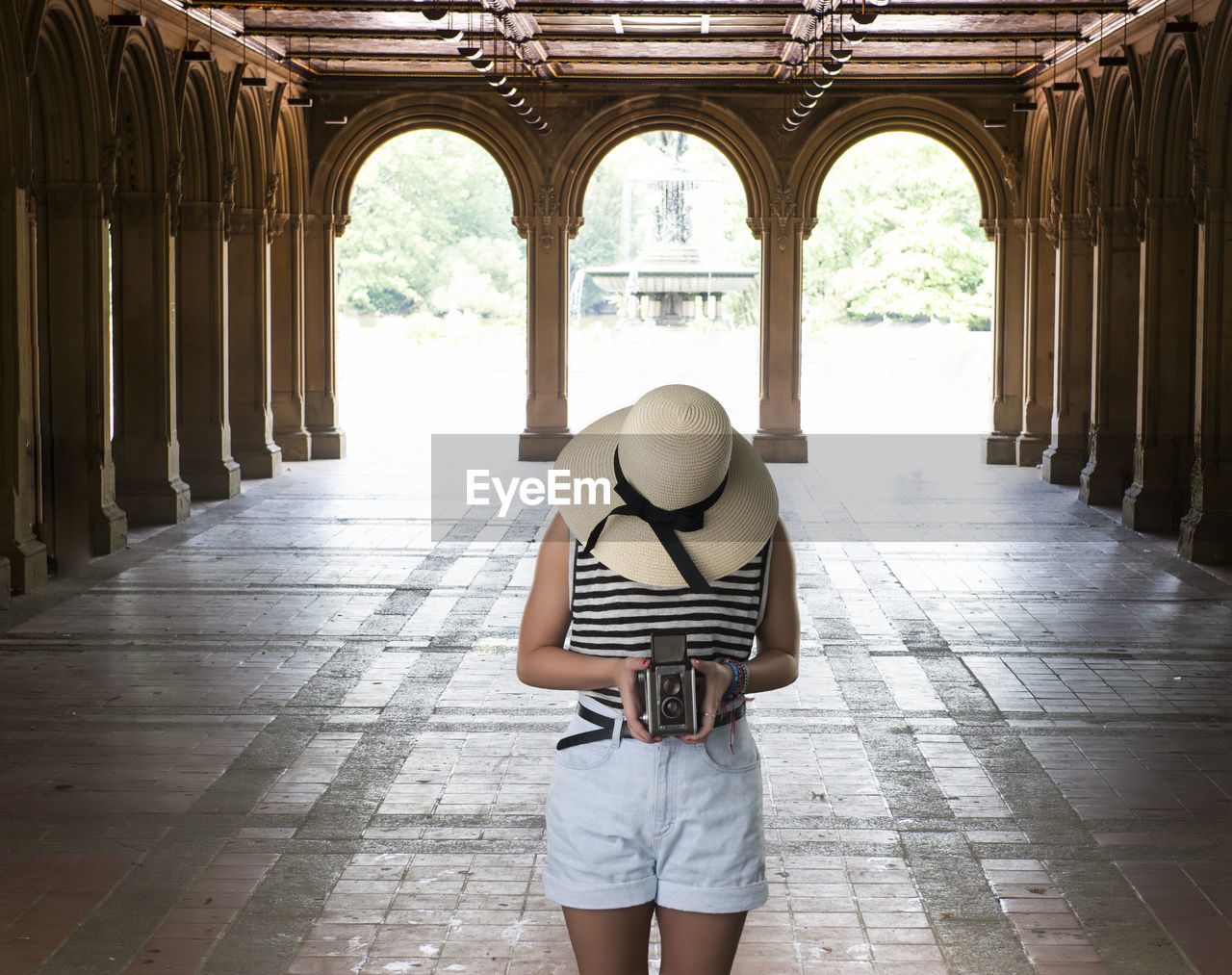 one person, real people, architecture, architectural column, day, lifestyles, built structure, casual clothing, leisure activity, arch, women, building, standing, indoors, holding, three quarter length, front view, adult, obscured face