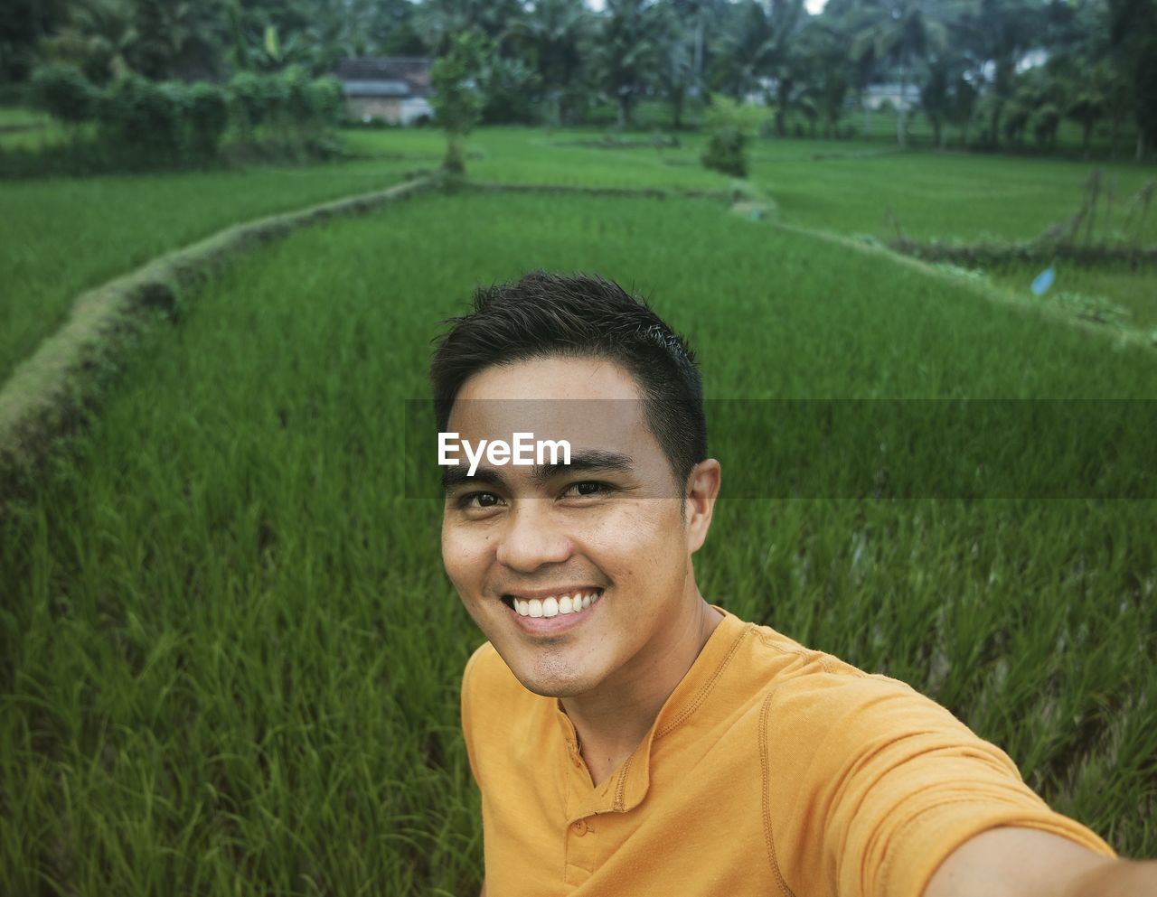 Portrait Of Smiling Young Man In Field