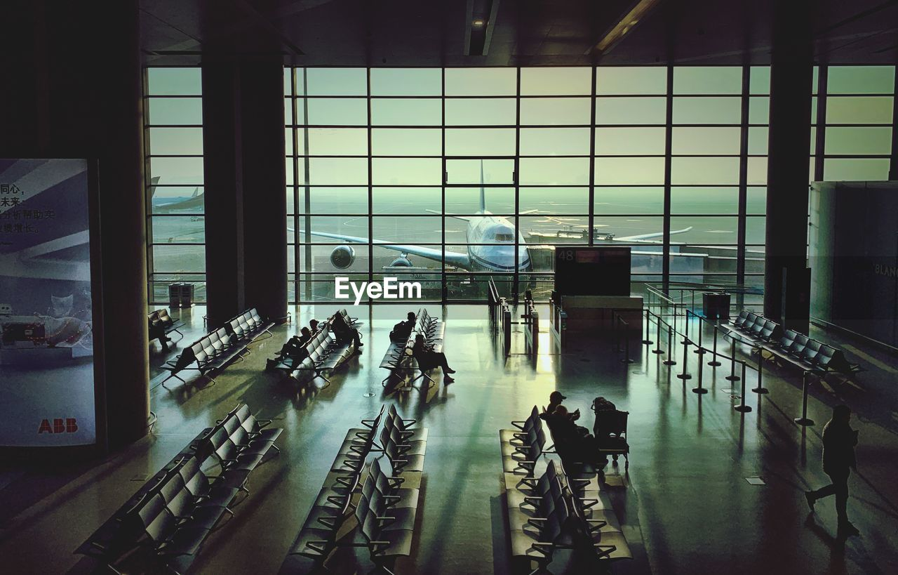 group of people, real people, architecture, transportation, indoors, travel, glass - material, window, men, built structure, large group of people, airport, crowd, lifestyles, journey, city, walking, high angle view, modern, flooring, airport departure area, airport terminal, station
