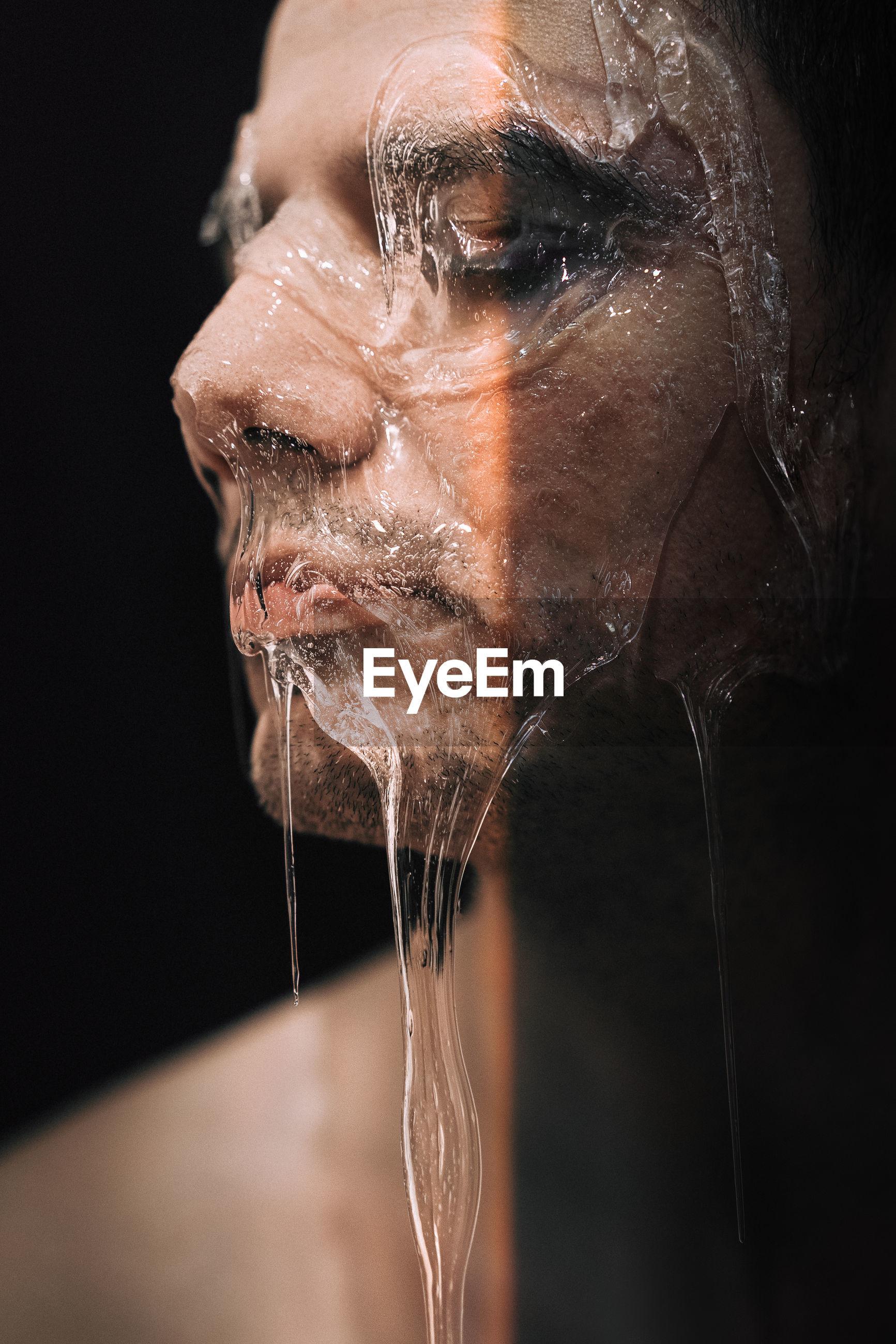 Close-up of gel on man face in darkroom