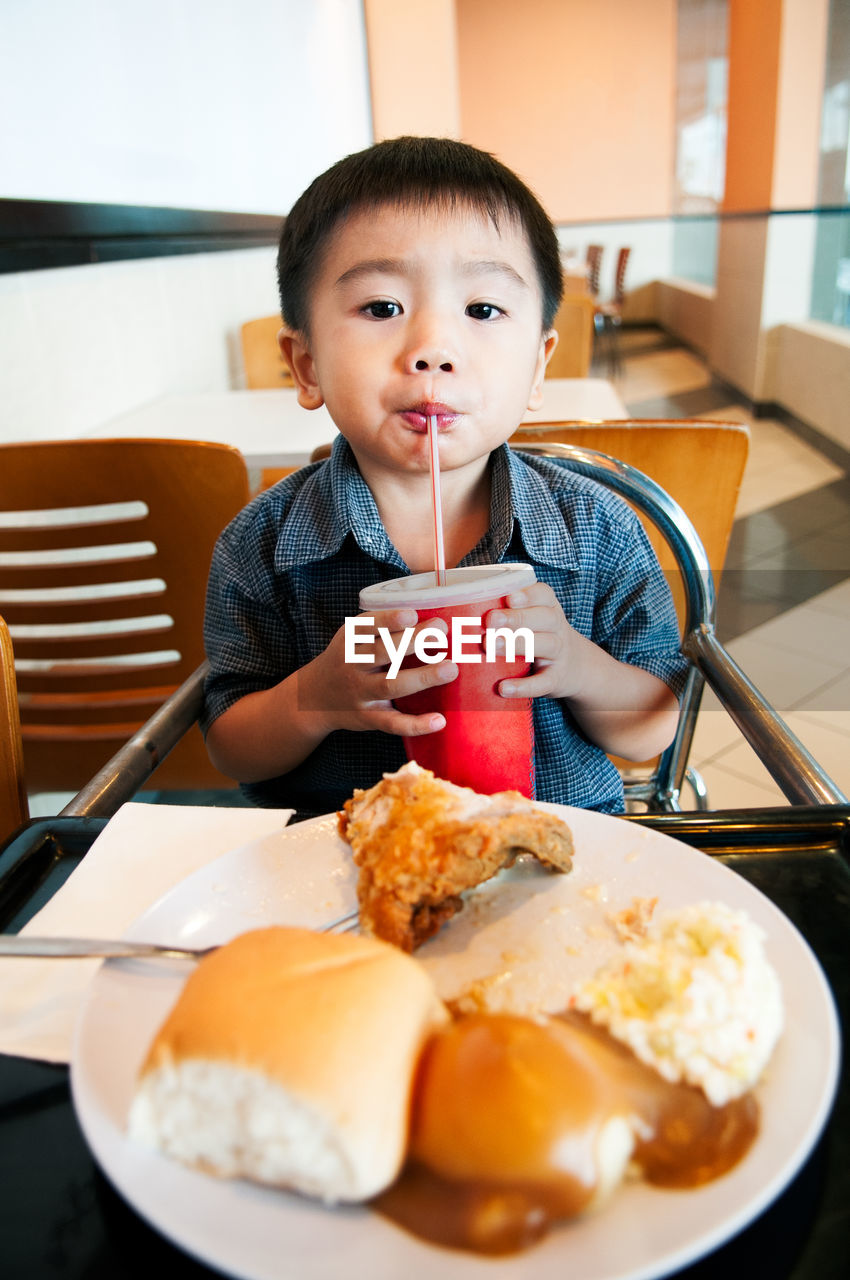 Portrait of boy eating food on table