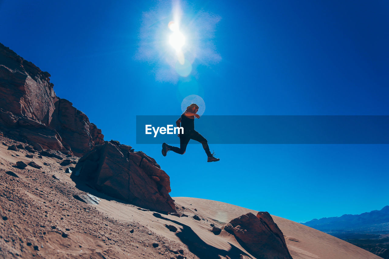 Low angle view of young man jumping on mountain against blue sky during sunny day