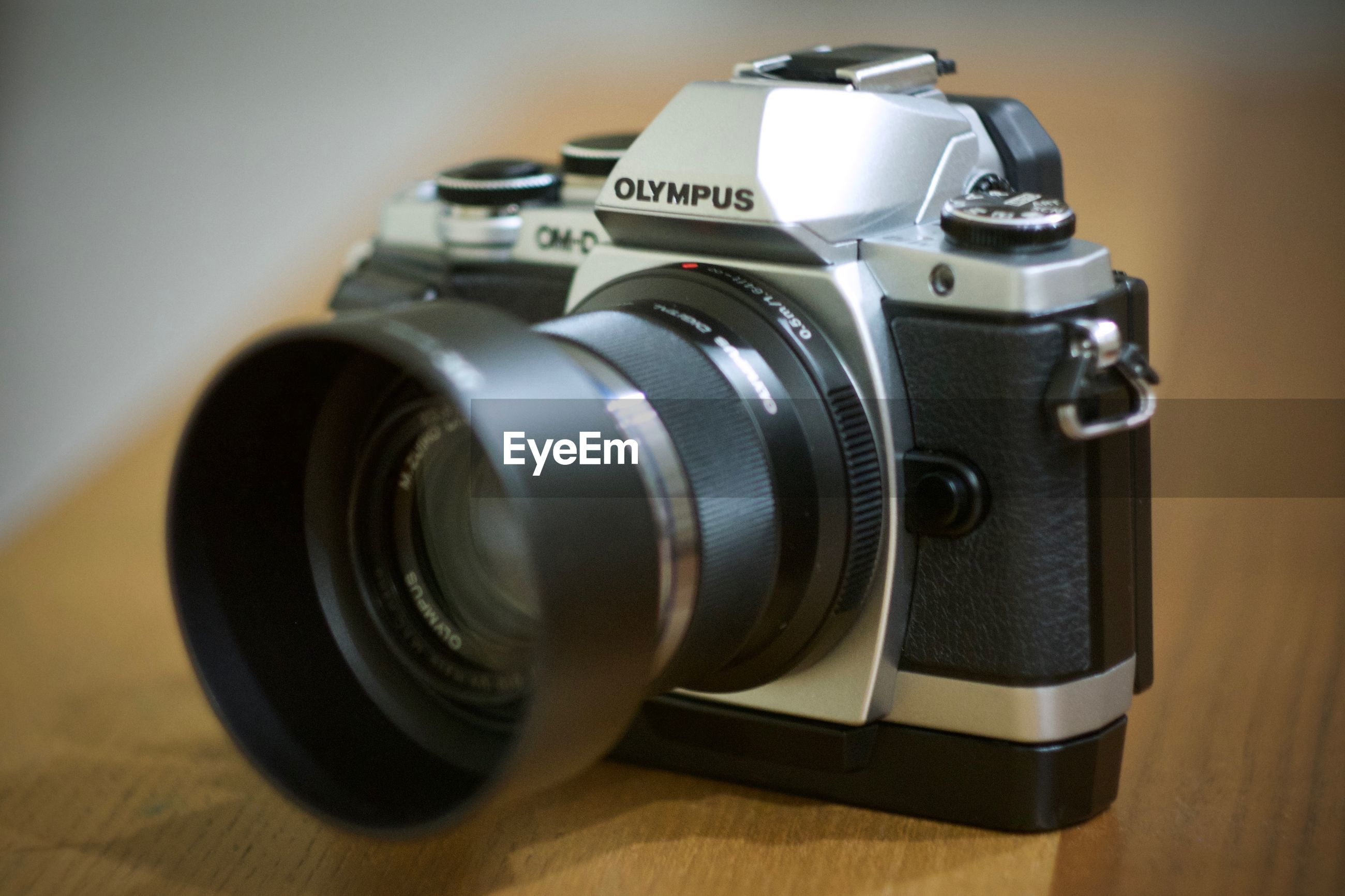 CLOSE-UP OF CAMERA ON TABLE WITH EYEGLASSES