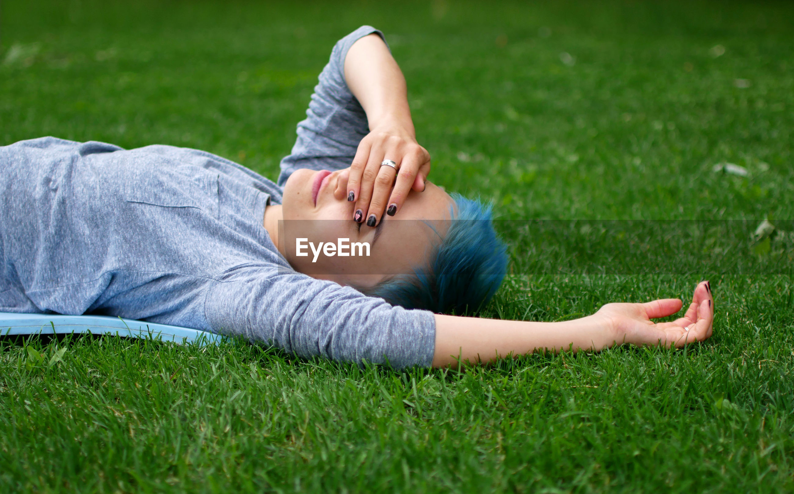Side view of woman covering eyes while lying on field at park