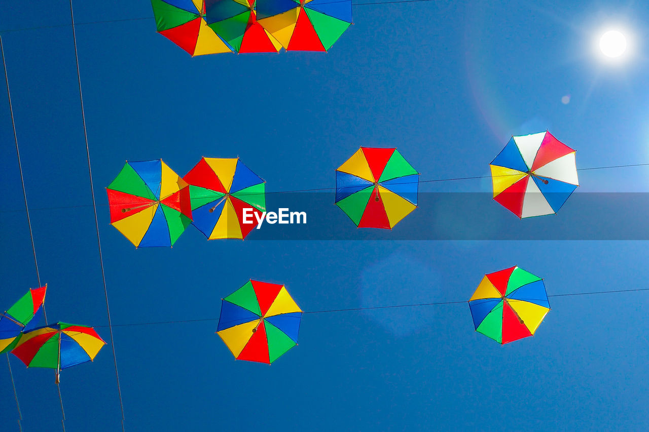 Low Angle View Of Colorful Umbrellas Hanging Against Clear Blue Sky During Sunny Day