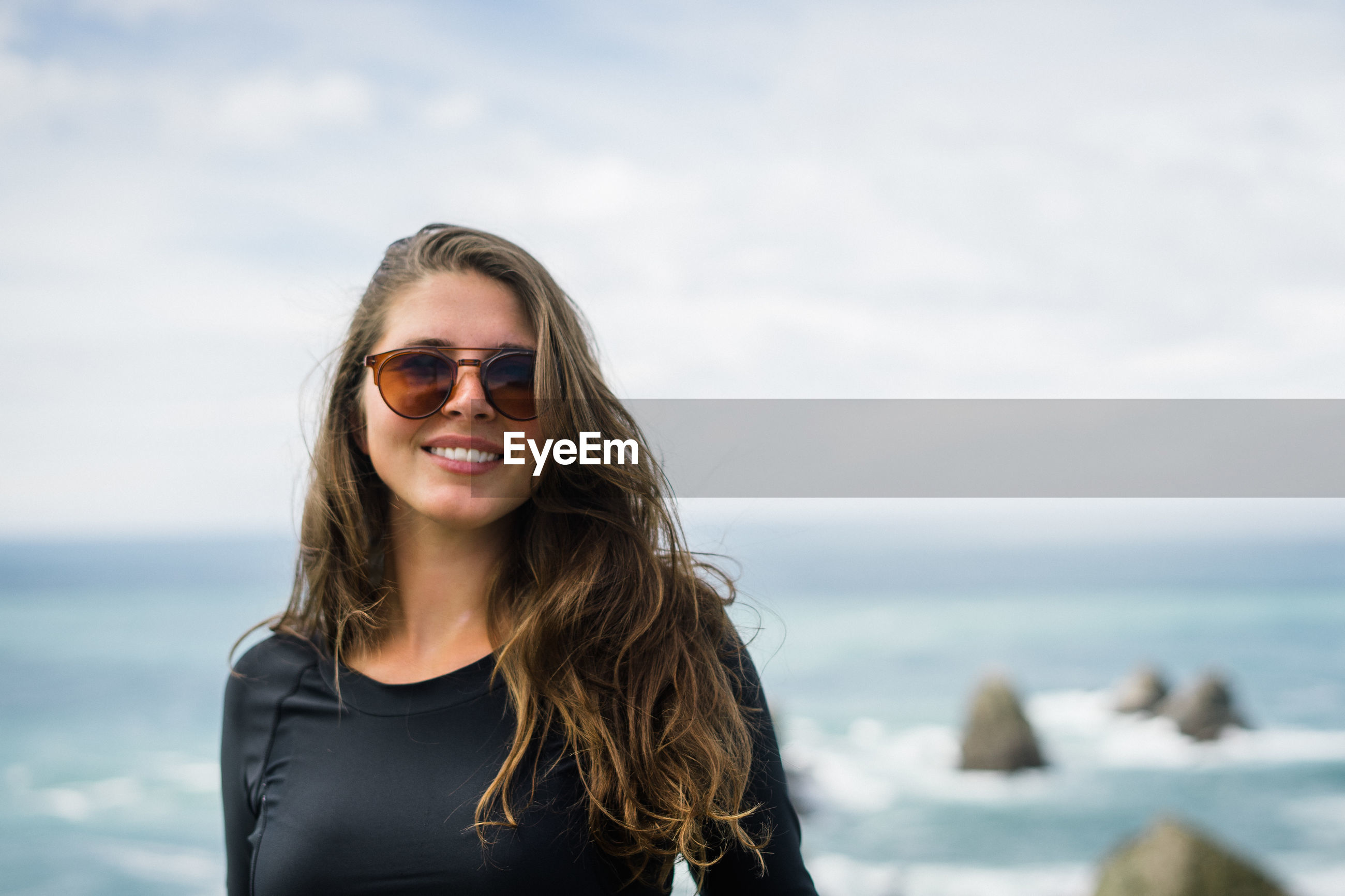 Smiling young woman standing at beach