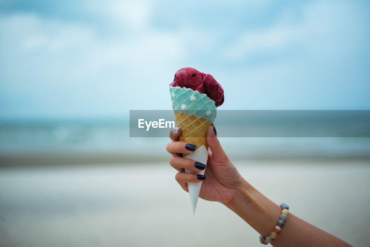 Cropped Hand Of Woman Having Ice Cream Cone At Beach
