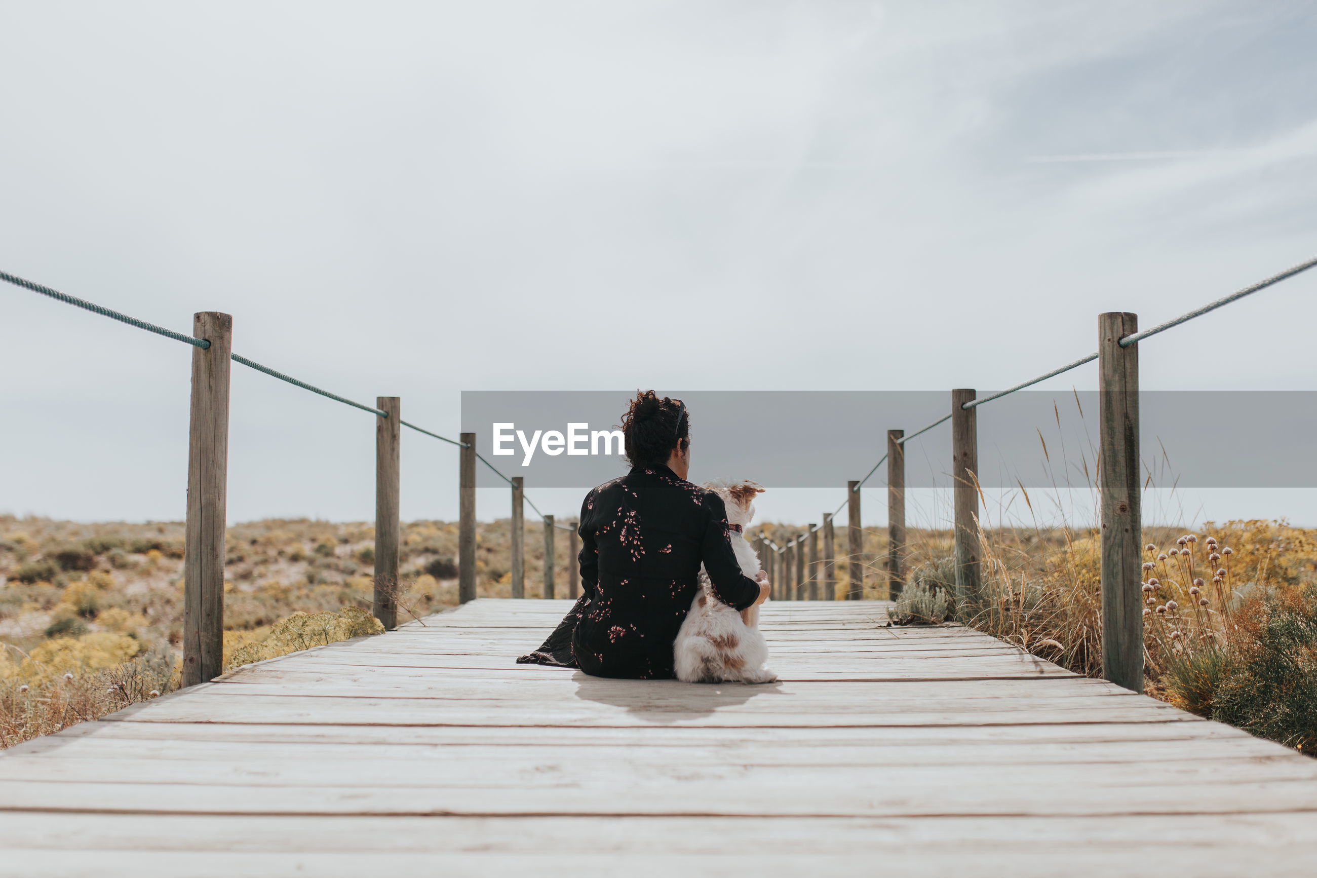 Woman sitting on railing against sky