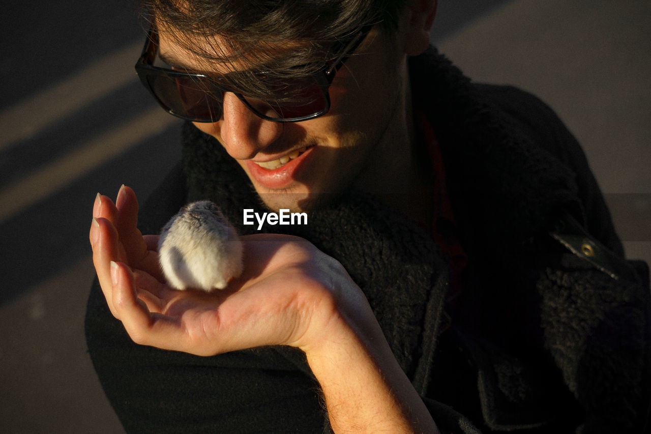 Smiling young man wearing sunglasses while holding hamster