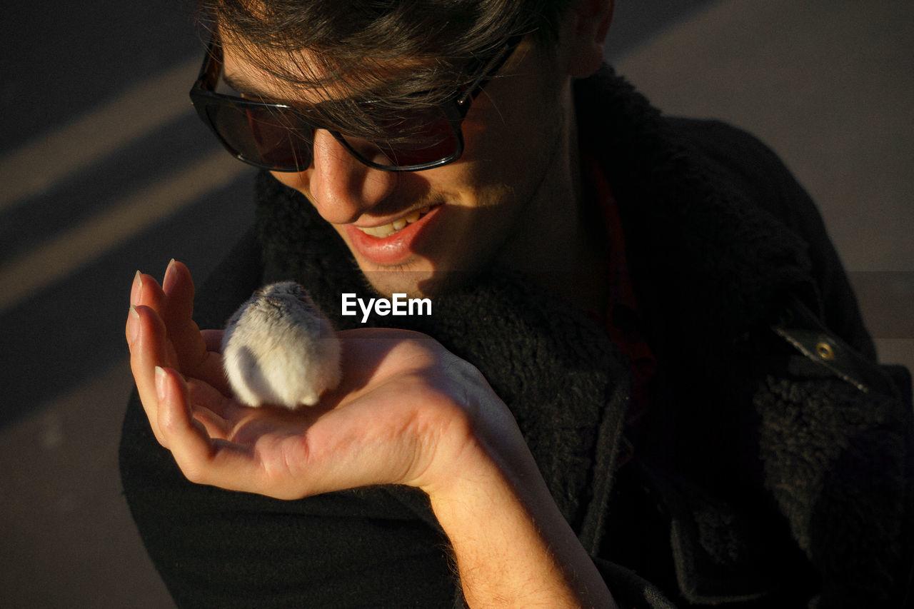 Close-Up Portrait Of Man Holding Mouse