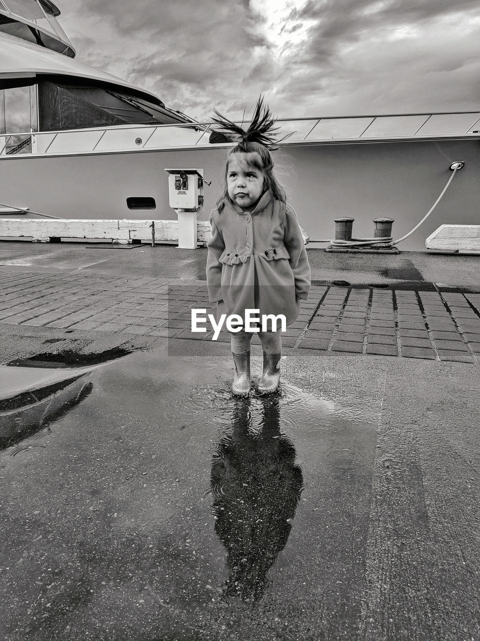 Cute girl standing on road against sky