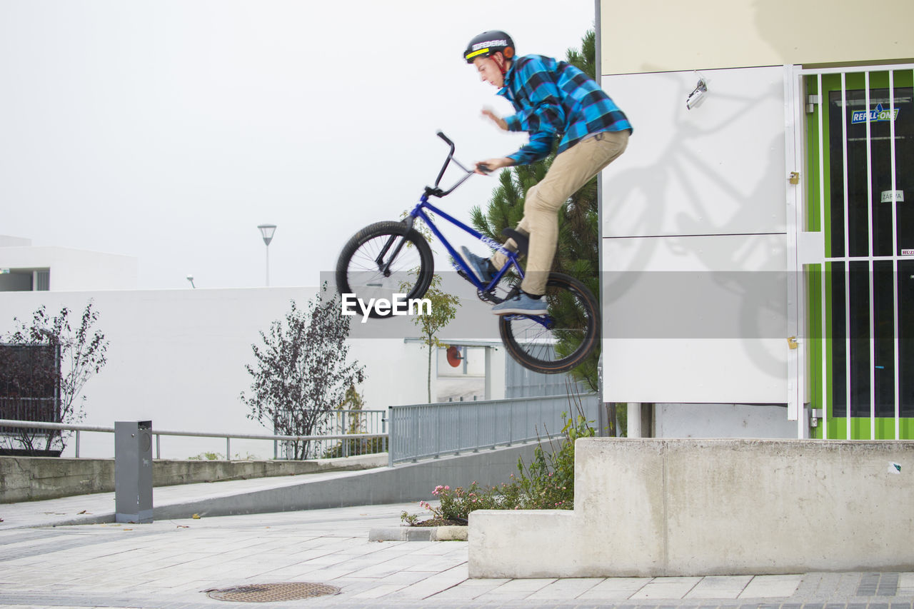 bicycle, leisure activity, bmx cycling, stunt, real people, skill, full length, one person, built structure, outdoors, skateboard park, sports ramp, day, helmet, cycling, risk, lifestyles, casual clothing, sport, extreme sports, cycling helmet, adventure, headwear, men, young adult, city, people