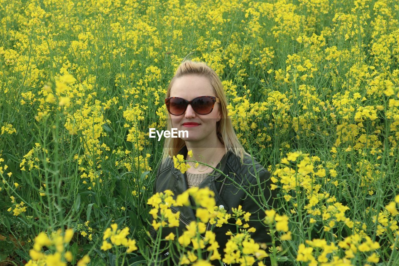 Woman standing in field of yellow flowers