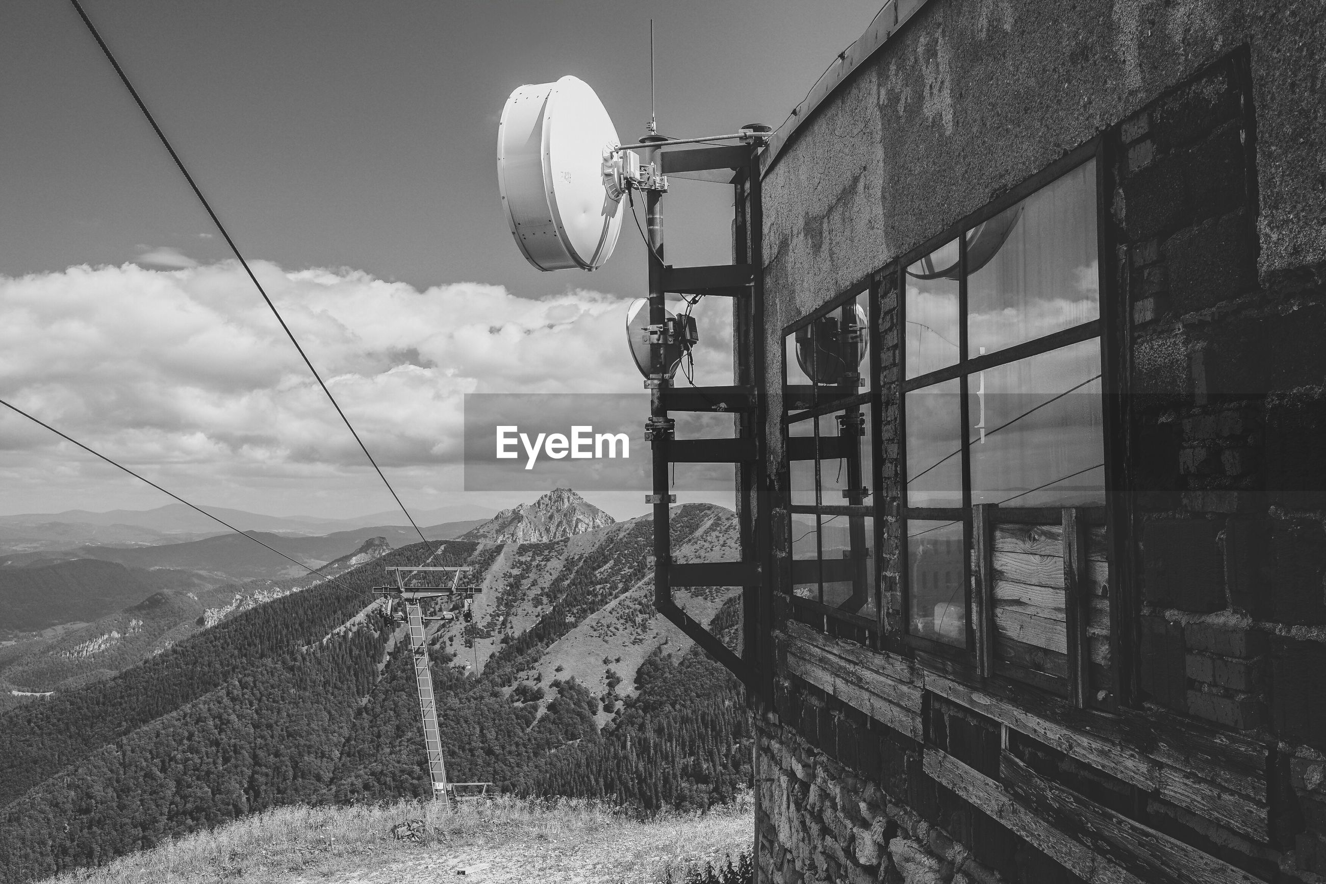 Satellite dishes on building against mountains