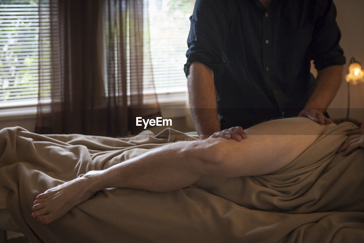 Midsection Of Man Giving Massage To Customer