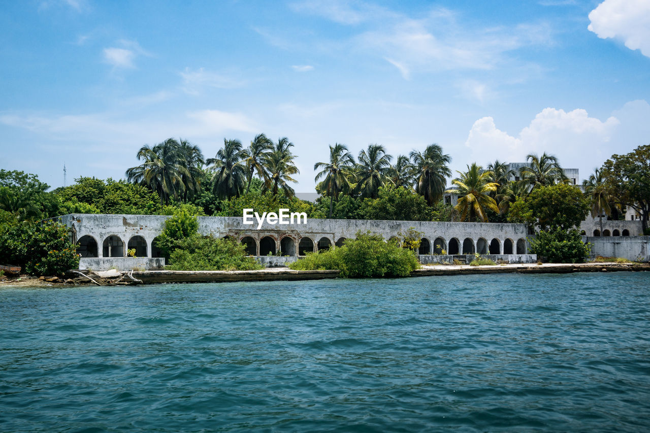 water, tree, sky, plant, built structure, waterfront, architecture, nature, cloud - sky, day, no people, beauty in nature, building exterior, scenics - nature, palm tree, tropical climate, growth, sea, outdoors