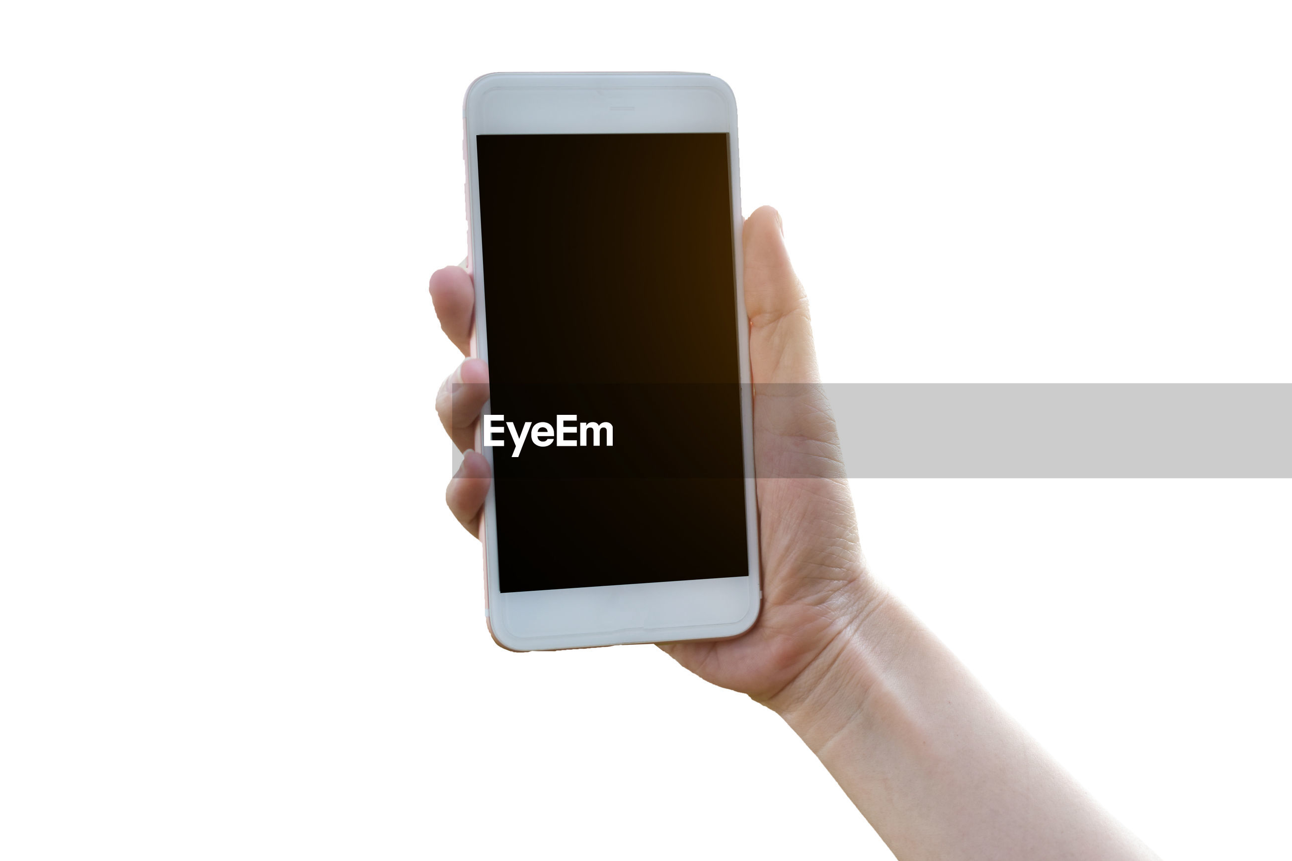Close-up of hand holding mobile phone over white background