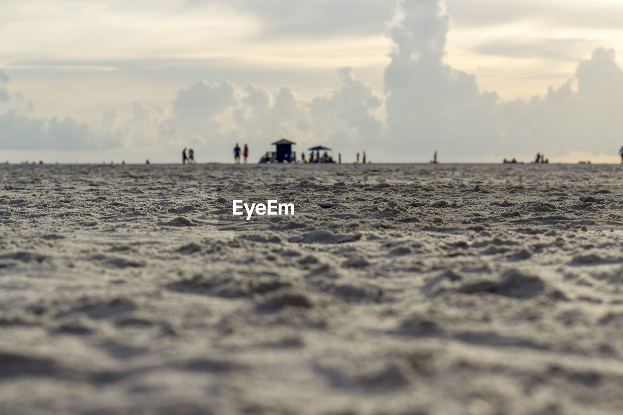 sky, water, sea, land, waterfront, nature, beach, cloud - sky, scenics - nature, beauty in nature, group of people, incidental people, selective focus, tranquility, outdoors, day, tranquil scene, horizon, real people, horizon over water, surface level