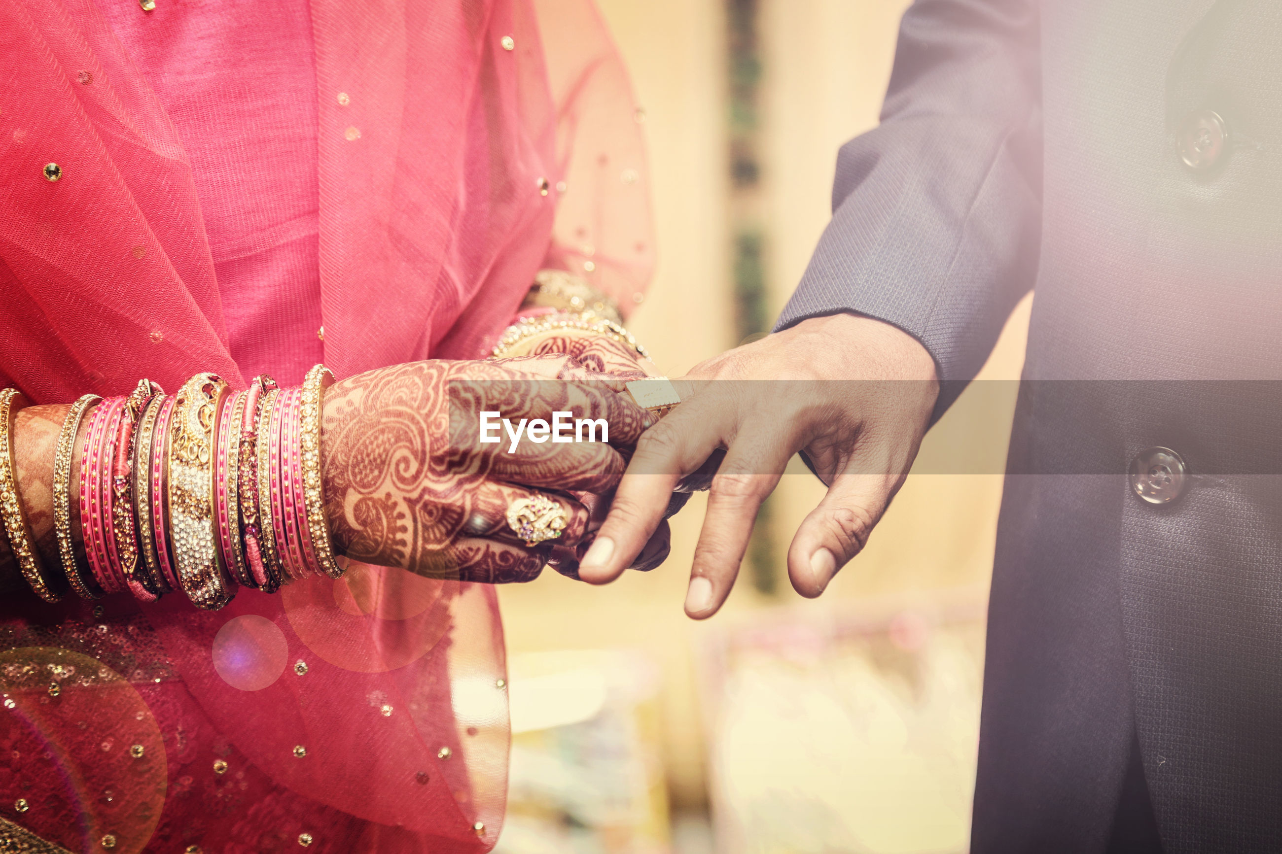 Midsection of bride putting ring on bridegroom during wedding