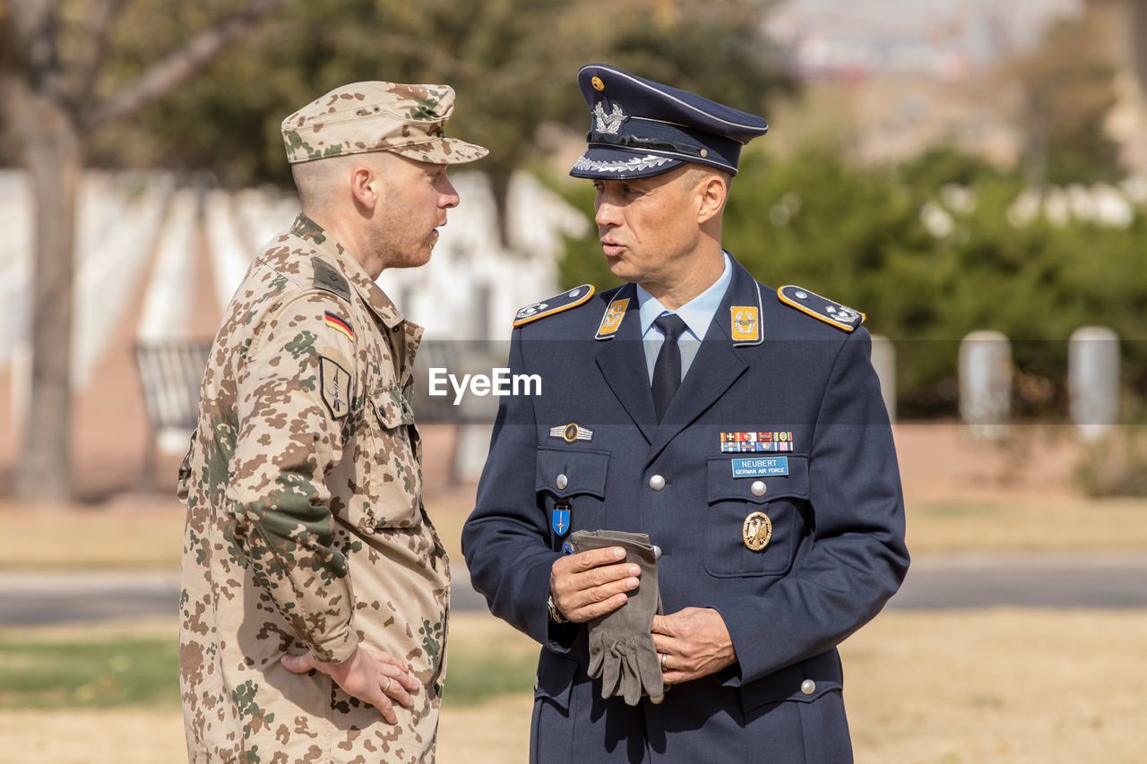 uniform, government, clothing, military uniform, military, armed forces, army soldier, men, standing, two people, focus on foreground, males, army, day, patriotism, emotion, people, mature adult, mature men, outdoors, badge, responsibility