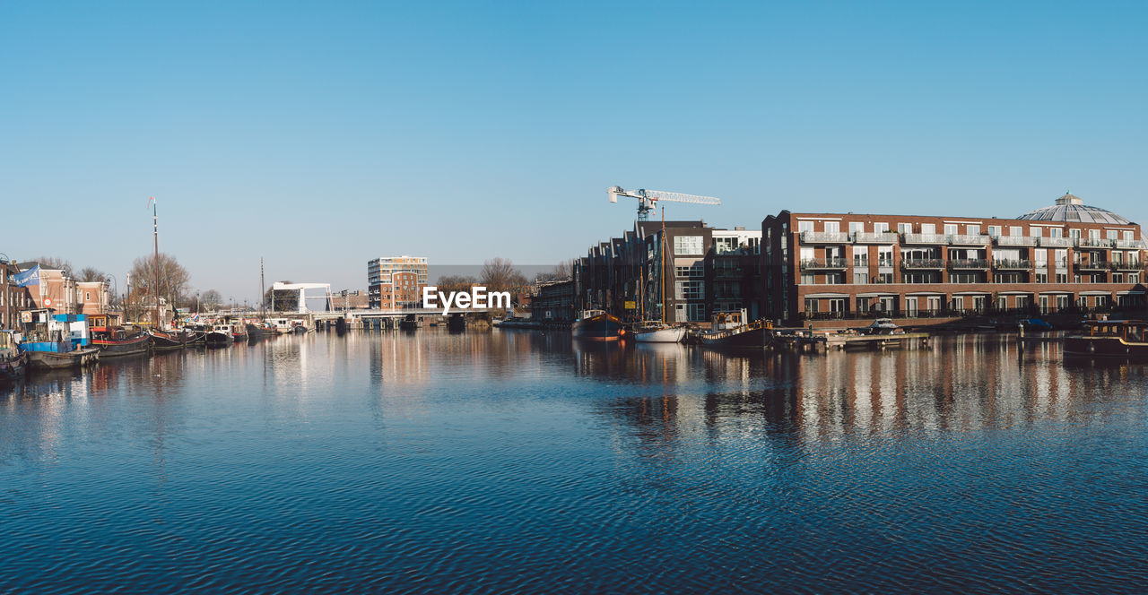 architecture, building exterior, built structure, water, clear sky, waterfront, nautical vessel, reflection, outdoors, city, day, no people, moored, blue, travel destinations, sky, cityscape
