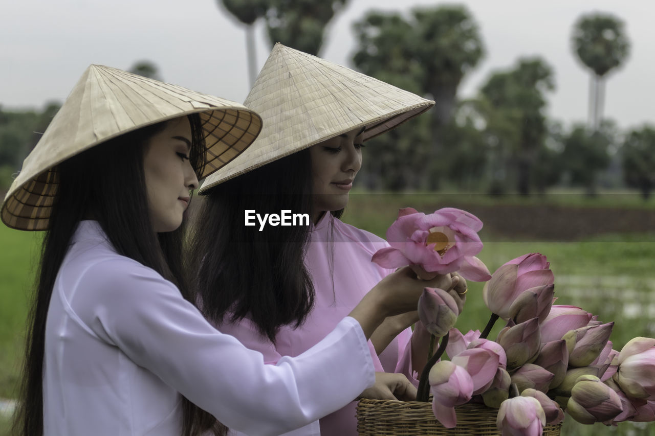 Female friends wearing asian style conical hats holding flowers