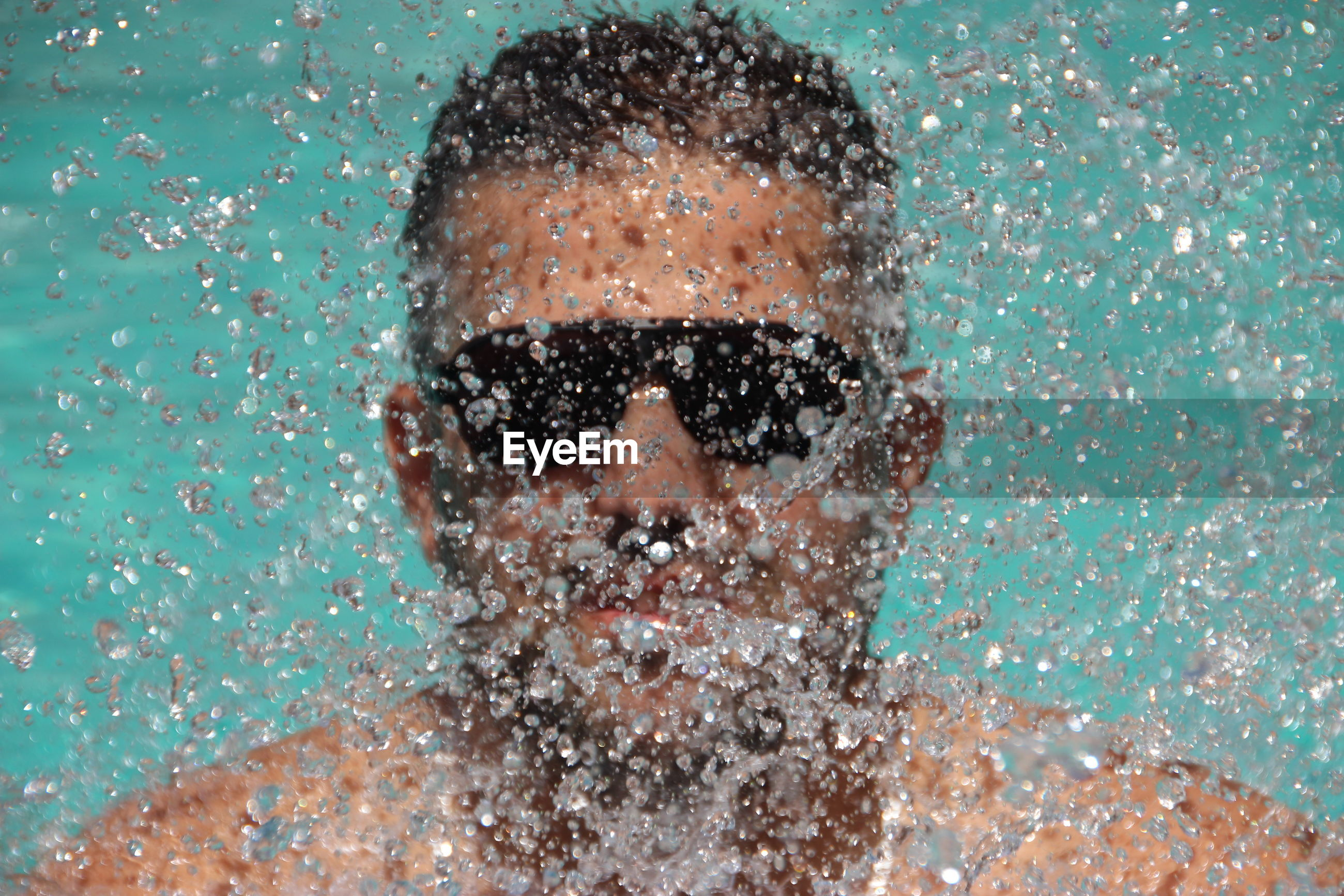 Close-up portrait of man wearing sunglasses in swimming pool